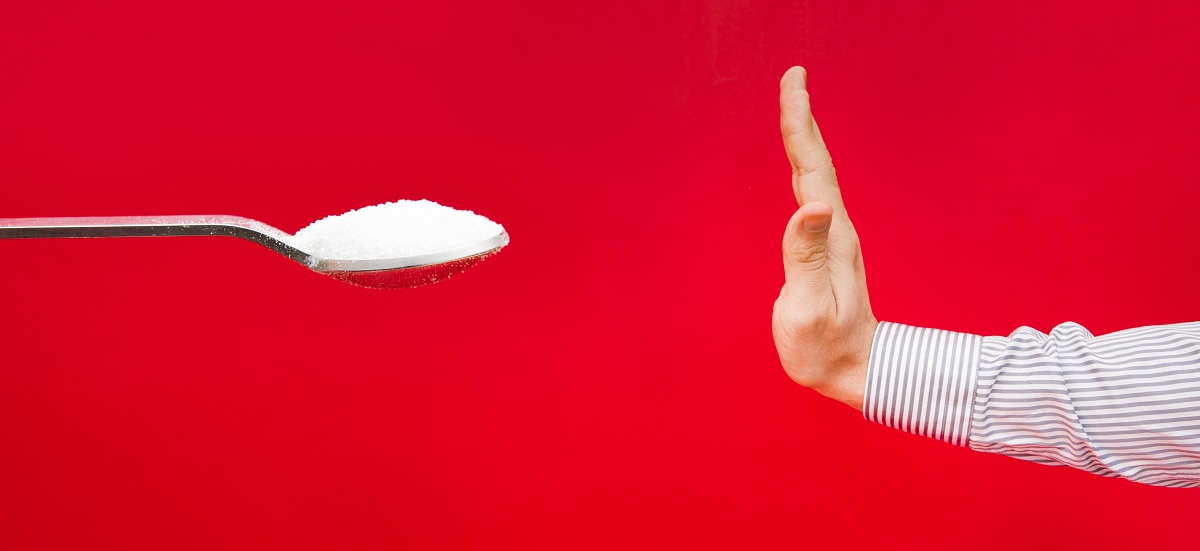 Saying no tu sugar suggested by a hand refusing a teaspoon