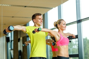 smiling man and woman with dumbbells in gym